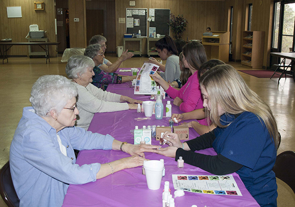 cosmetology students giving free manicures to senior citizens